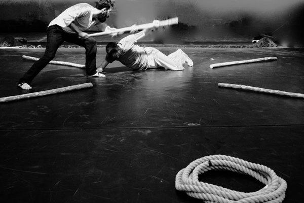 foto in bianco e nero: i due danzatori vengono immortalati mentre danzano; uno dei due è a terra. Sulla scena una corda e dei bastoni.