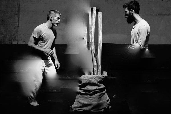 foto in bianco e nero: i due danzatori vengono immortalati mentre danzano; si guardano e tra loro vi sono dei bastoni in posizione verticale.