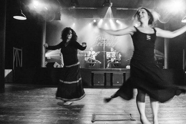 foto in bianco e nero; due danzatrici ballano con sullo sfondo i musicisti in concerto.