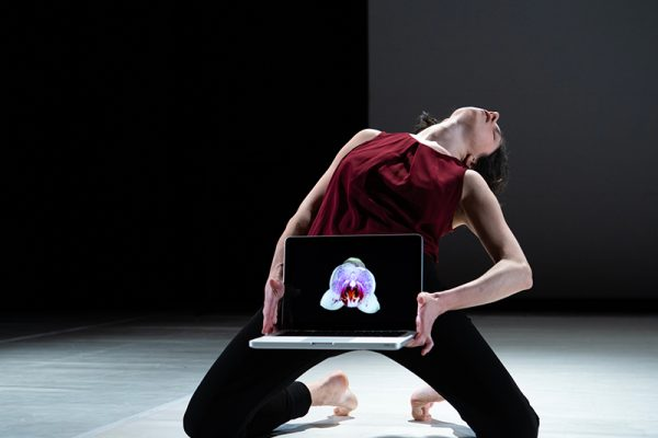 donna in ginocchio con testa reclinata e un pc portatile aperto sulle ginocchia