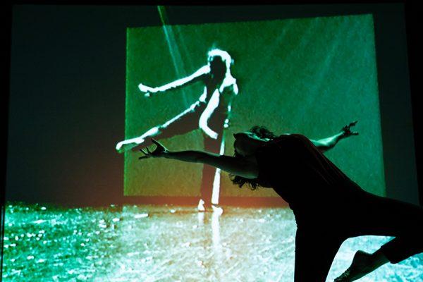 una donna che danza, sullo sfondo la proiezione di una donna che danza