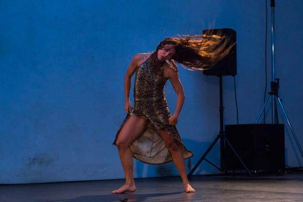 la danzatrice è immortalata mentre danza, la posizione è frontale. La luce nella sala ha una tonalità tendente al blu.