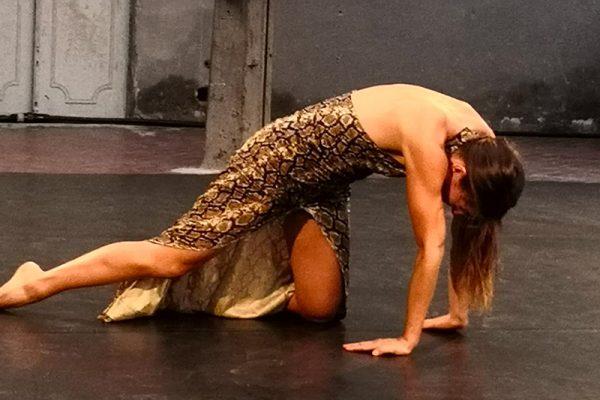 una ragazza (la danzatrice) è a terra in una posa di danza, indossa un abito lungo. La performance si svolge in uno spazio interno, sullo sfondo un muro e una porta che mostrano i segni del tempo.