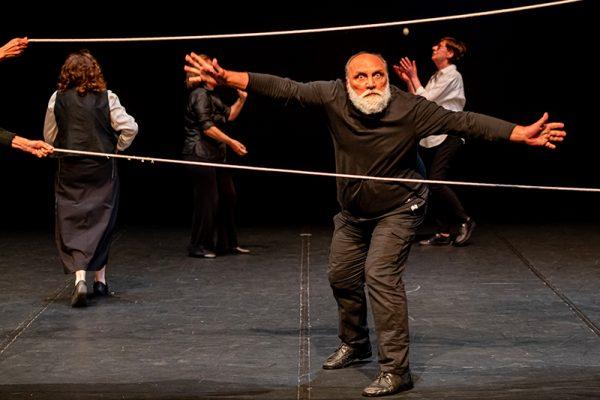 due fili tesi, un uomo con barba bianca e abiti neri danza