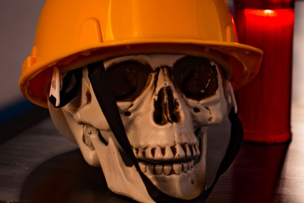 """un finto cranio umano che """"indossa"""" un casco giallo da cantiere. Al suo fianco è acceso un lumino votivo di colore rosso."""