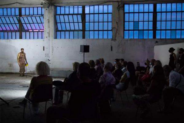 in uno spazio interno di tipologia industriale viene ripresa di scorcio parte del pubblico, in fondo il danzatore.