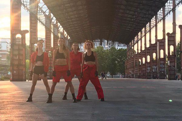 quattro danzatori vestiti di rosso in un capannone